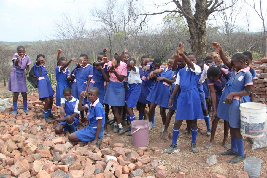 These girls are breaking rocks to cover their schoolyard